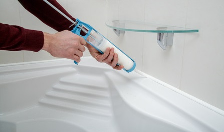 60224967 - man hands applying silicone sealant with caulking gun.